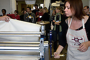 """O.U. student Annette Gasper rolls a press during the 2006 Mid America Print Council conference """"Forging Connections"""" at Ohio University on Friday, 9/22/06. The conference runs from September 20-23. Around 700 printmakers, students, curators and other art professionals are expected to attend the biennial event."""