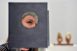 "© Licensed to London News Pictures. 15/06/2017. London, UK. A staff member is seen looking through ""Four-Square (Four Circles)"", 1966, by Barbara Hepworth (estimate GBP200-300k).   Preview of Impressionist and Modern art sale, which will take place at Sotheby's New Bond Street on 21 June.  Photo credit : Stephen Chung/LNP"