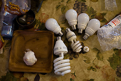 Energy efficient lightbulbs supplied by CAASM sit on a clients table before being installed.