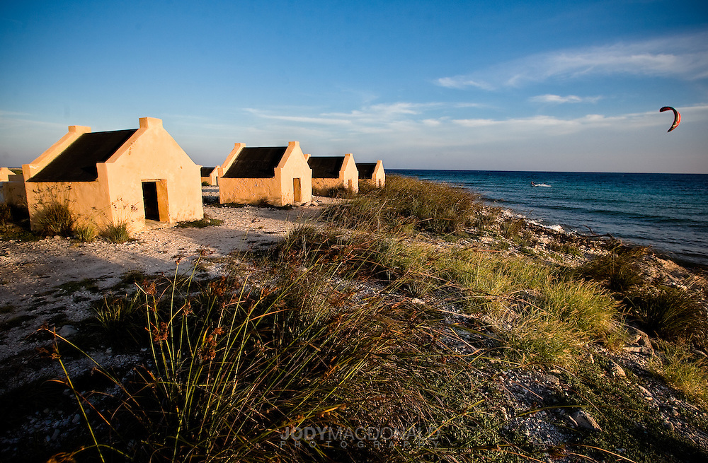 On the southern tip of Bonnaire, in the Netherlands Antilles lies a row of huts that once housed slaves that worked in the salt mines on the island.  The winds in Bonnaire blow consistently over the island and the contrast between the ancient huts and modern kitesurfer grabbed my eye.