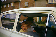 A young boy sits in the family Anglia car with his older sister on an Essex estate in the early nineteen sixties.