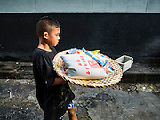 30 AUGUST 2016 - BANGKOK, THAILAND: A child leaves the Poh Teck Tung shrine with a basket full of food on the last day of Hungry Ghost Month in Bangkok. Chinese temples and shrines in the Thai capital host food distribution events during Hungry Ghost Month, during the 7th lunar month, which is usually August in the Gregorian calendar.        PHOTO BY JACK KURTZ