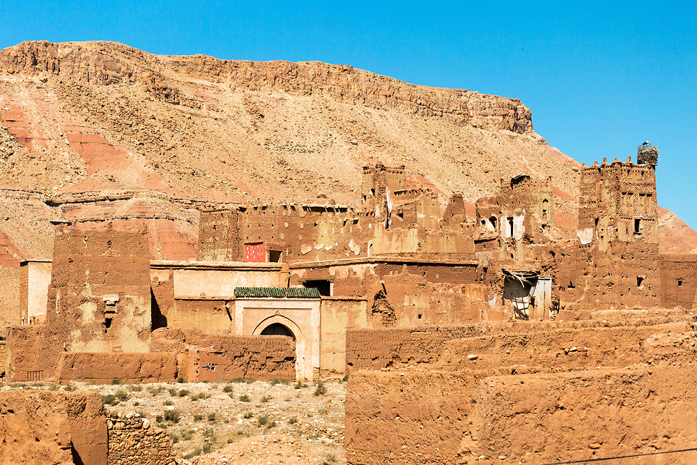 """Berber Village, Ounila Valley (connecting Ait BenHaddou to Telouet Kasbah) Ouarzazate Province, Morocco Morocco, 2016-04-23.<br /><br />The Ounila Valley links the Tizi n Tichka pass to Ait Ben Haddou and was originally the main thoroughfare for the trans-saharan trade route between Marrakesh and sub-saharan Africa. Today, evidence of this once highly important role is reflected in the numerous crumbling kasbah's and ksar which are dotted all throughout the valley. <br /> <br /> The famous ksar of Ait ben Haddou stands at one entrance to the valley (Ouarzazate direction) while the Telouet Kasbah of Thami El Glaoui – once Pasha of Marrakesh and the southern regions – stands at the other (just before the road links back up to the N9 highway). All the kasbah's and ksar inside the valley were built by families of high status and would have had the privilege of receiving gifts from across the world as a sort of tax for using the road.<br /> The Ounila river (Oued Ounila) brings life to the otherwise arid and dry land, forming a green, meandering river of lush plantations wherever the water flows. As you drive the road, scaling up and down in altitude, each turn will provide another stunning view over the green oasis which runs through the centre of the valley walls. <br /> The valley is best visited in the spring when the cherry trees are in bloom and everything is nourished from the rains in earlier months, the Ounila is a remarkable display of southern Moroccan architecture, with tiny pisé villages and mosques stacked up into the valley walls while kasbah's and ksar slowly erode back into the red tinted earth alongside them.<br /> Ait ben Haddou certainly isn't a """"hidden gem"""" in Morocco. It's been used as a backdrop in blockbuster cinema and is one of the most visited tourist attractions the country has to offer. Many visitors find themselves unable to head on into the Ounila Valley towards Telouet. This is partly due to the road being in bad condition and also due to """