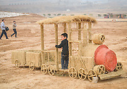 LUOYANG, CHINA - MARCH 16: (CHINA OUT) <br /> <br /> A child plays on a straw vehicle at a construction site on March 16, 2016 in Luoyang, Henan Province of China. Various straw dolls like dinosaurs, ducks, Minions, elephants, pandas and small trains as well we others are made at a construction site which attracted citizens and visitors.<br /> ©Exclusivepix Media