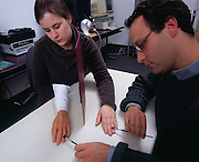 Dr. Mathew Botvinick with research assistant performing the rubber hand experiment.  After 10 minutes of observing the rubber hand getting the same brush stroke as their real hand  the subject perceives the rubber hand as their own.