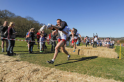 © Licensed to London News Pictures. 16/03/2014. Dorking, UK. The 7th UK Wife Carrying Race. Males or females carry a 'wife' over a 380M course which features obstacles and water hazards. The wives must be at least 18yrs old, male or female and weigh at least 50kg. The last placed finishers receive a ceremonial Pot Noodle and dog food. Picture shows eventual winner Rich Blake Smith carrying Anna who completed the course in 2 minutes 0 seconds. Photo credit : Julie Edwards/LNP