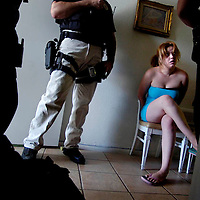 Rialto Police Department's Multiple Enforcement Team and Narcotics Officers conduct a raid on two Rialto massage and tanning parlors suspected of prostitution, this 21-year-old detained was sited and released, Wednesday, July 1, 2006. Eric Reed/Staff photographer