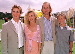 MR & MRS MIKE RUTHERFORD, he is the musician and their sons left, TOM RUTHERFORD and right, HARRY RUTHERFORD, at a polo match in Sussex on 23rd July 2000.OGI 173