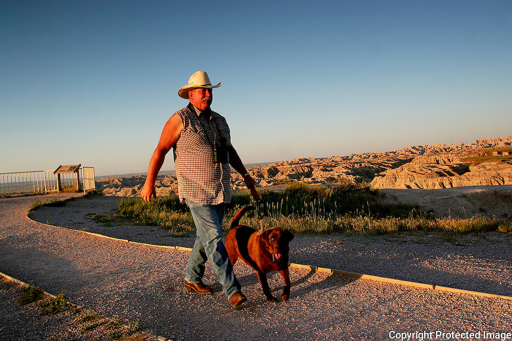 A man takes his dog for an early morning walk in Badlands National Park in South Dakota.