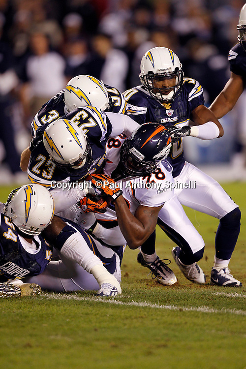 Denver Broncos running back Correll Buckhalter (28) gets gang tackled by San Diego Chargers linebacker Stephen Cooper (54), San Diego Chargers cornerback Quentin Jammer (23), and San Diego Chargers safety Eric Weddle (32) during the NFL week 11 football game against the San Diego Chargers on Monday, November 22, 2010 in San Diego, California. The Chargers won the game 35-14. (©Paul Anthony Spinelli)