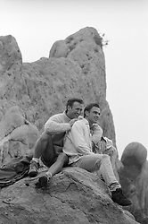gay couple sitting on rock formations in California