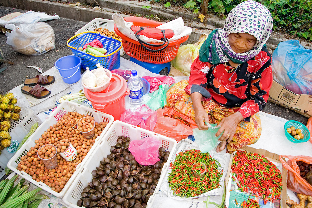 An old Malaysian woman selling fruit and vegetables at a market in Malaysia..
