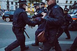 London, May 27th 2015. A protester is arrested as dozens  demonstrate outside Downing Street against the Tories' ongoing campaign of austerity on the day the Queen delivered her speech to Parliament