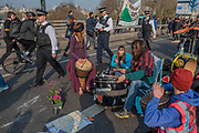 Playing music to commuters and the police - Morning on Waterloo Bridge sees the camp awake and commuters make their progress on foot and bike across the river - Day 3 - Protestors from Extinction Rebellion block several junctions in London as part of their ongoing protest to demand action by the UK Government on the 'climate chrisis'. The action is part of an international co-ordinated protest.
