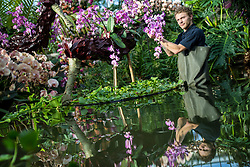 © Licensed to London News Pictures. 07/02/2019. London, UK. Kew Garden Diploma Student Michael Antonetti tends to some hanging orchids at the 24th annual Kew Orchid Festival, which this year focusses on the colour and biodiversity of Colombia. Photo credit: Rob Pinney/LNP