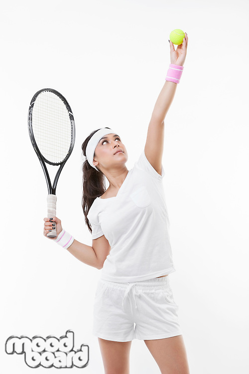 Young female tennis player preparing to serve ball against white background