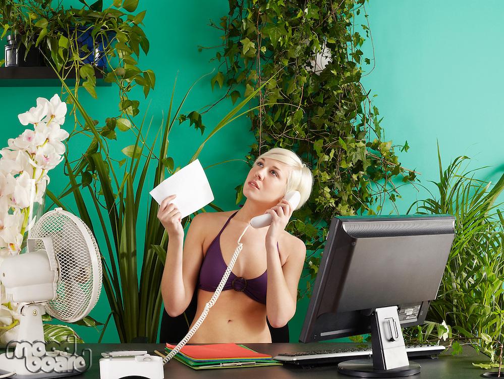 Female office worker on phone wearing bikini