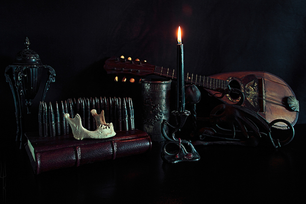 An arrangement of antiques, including bullets, a human jaw bone, and an early American mandolin set on a dark background.
