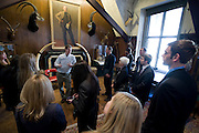 Adventurer Scott Hamilton with guests in the Trophy Room of the club, New York City...Founded in New York City in 1904, The Explorers Club promotes the scientific exploration of land, sea, air, and space by supporting research and education in the physical, natural and biological sciences. The Club's members have been responsible for an illustrious series of famous firsts: First to the North Pole, first to the South Pole, first to the summit of Mount Everest, first to the deepest point in the ocean, first to the surface of the moon--all accomplished by our members.