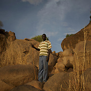 April 28, 2012 - Buram, Nuba Mountains, South Kordofan, Sudan: A Nuba man stands among rocks in the mountains outside Buram village in South Kordofan's Nuba Mountains. Since the 6th of June 2011, the Sudan's Army Forces (SAF) initiated, under direct orders from President Bashir, an attack campaign against civil areas throughout the South Kordofan's province. Hundreds have been killed and many more injured...Local residents, of Nuba origin, have since lived in fear and the majority moved from their homes to caves in the nearby mountains. Others chose to find refuge in South Sudan, driven by the lack of food cause by the agriculture production halt due to the constant bombardments of rural areas.