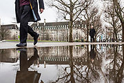 UNITED KINGDOM, London: 10 April 2018. People brave further miserable weather this morning as they walk and cycle past a large puddle along Southbank, London. The wet weather is set to continue until the weekend. Rick Findler / Story Picture Agency
