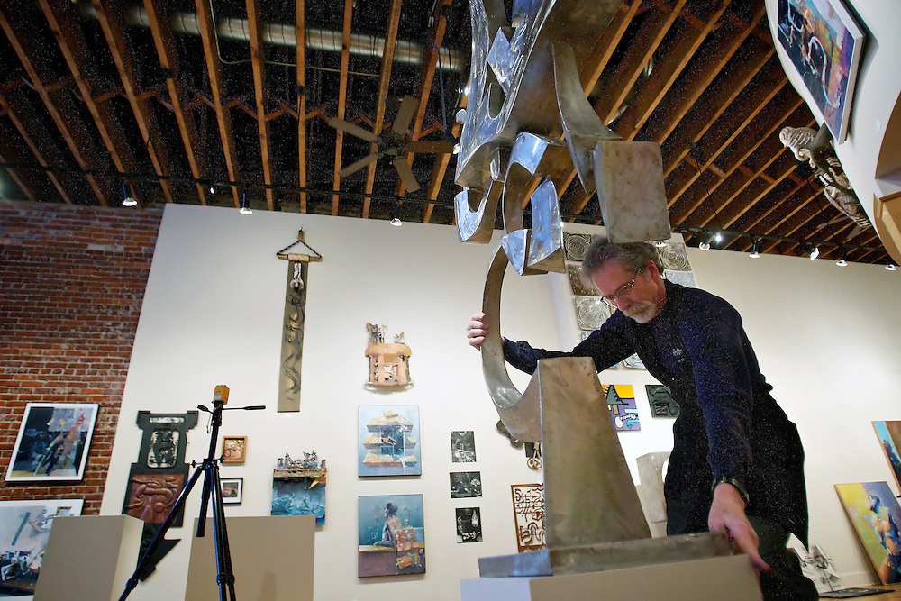 "Steve Gibbs, owner of The Art Spirit Gallery of Fine Art, repositions a Harold Balazs stainless steel sculpture Tuesday as he arranges his gallery for the ""Illuminating the Subconscious"" show which opens Friday."