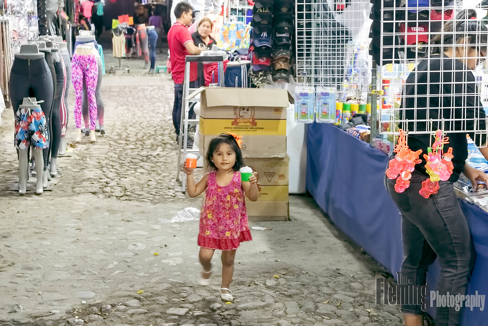 A young girl enjoys her ice cream at a festival in Bucerias, Nayarit, Mexico.
