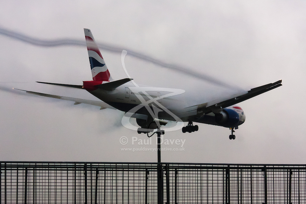 """January 3rd 2015, Heathrow Airport, London. Low cloud and rain provide ideal conditions to observe wake vortexes and """"fluffing"""" as moisture condenses over the wings of landing aircraft. With the runway visible only at the last minute, several planes had to perform a """"go-round"""", abandoning their first attempts to land. PICTURED: Wake vortices stream from the flaps of a British Airways Boeing 777 moments before it lands on Heathrow's runway 27L."""