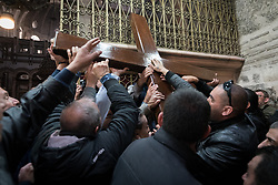 19 April 2019, Jerusalem: Members of the Latin Patriarchate of Jerusalem carry a wooden cross into the Church of the Holy Sepluchre. Thousands of Christians march the Via Dolorosa on Good Friday, marking the stations of the cross in the Jerusalem Old City, in memory of the path Jesus walked carrying his cross towards his crucifixion.