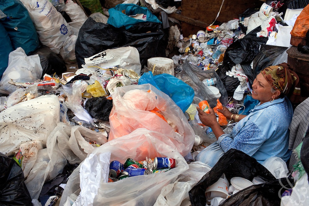 "An Egyptian woman sorts garbage into organic and inorganic piles in the Manshiyet Nasr neighborhood of Cairo, Egypt June 5, 2009. The majority coptic christian garbage collectors, known as ""zabbaleen"", (""garbage people"" in arabic), recently have had to adapt to a new way of working after the Egyptian government confiscated and killed all the pigs in their area. Pigs are important to the zabbaleen, since the pigs are used to dispose of all the organic bits of trash collected."