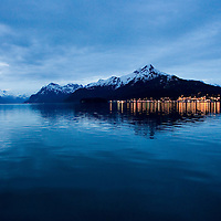 The city of Cordova, Alaska, sitting at the base of Mount Eyak, reflects an evening glow into Orca Inlet, on the eastern edge of Prince William Sound. Cordova is the home of the Eyak Tribe and the world famous Copper River salmon fishery. Prince William Sound was victim of the Exxon Valdez oil spill, and Cordova is home to the majority of commercial fishermen in the sound.
