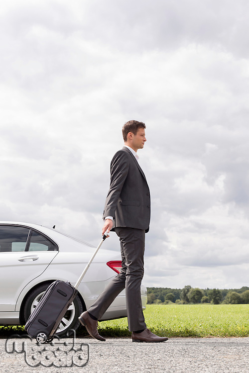 Full length side view of young businessman with luggage walking by broken down car at countryside