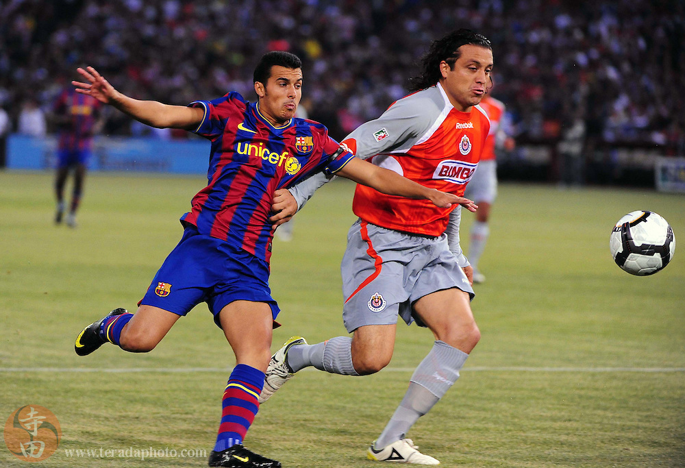 August 8, 2009; San Francisco, CA, USA; FC Barcelona defender Pedro Rodriguez (left) fights for the ball with Chivas de Guadalajara defender Hector Reynoso (right) during the first half in the Night of Champions international friendly contest at Candlestick Park.