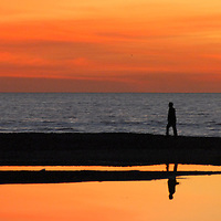 A person walks along the Santa Monica shoreline during the last sunset of 2009 on Thursday, December 31. 2009.