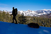 Backcountry skier silhouetted against Sierra peaks en route to Glacier Point, Yosemite National Park, California