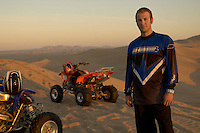 Man standing by quad bikes in desert at sunset