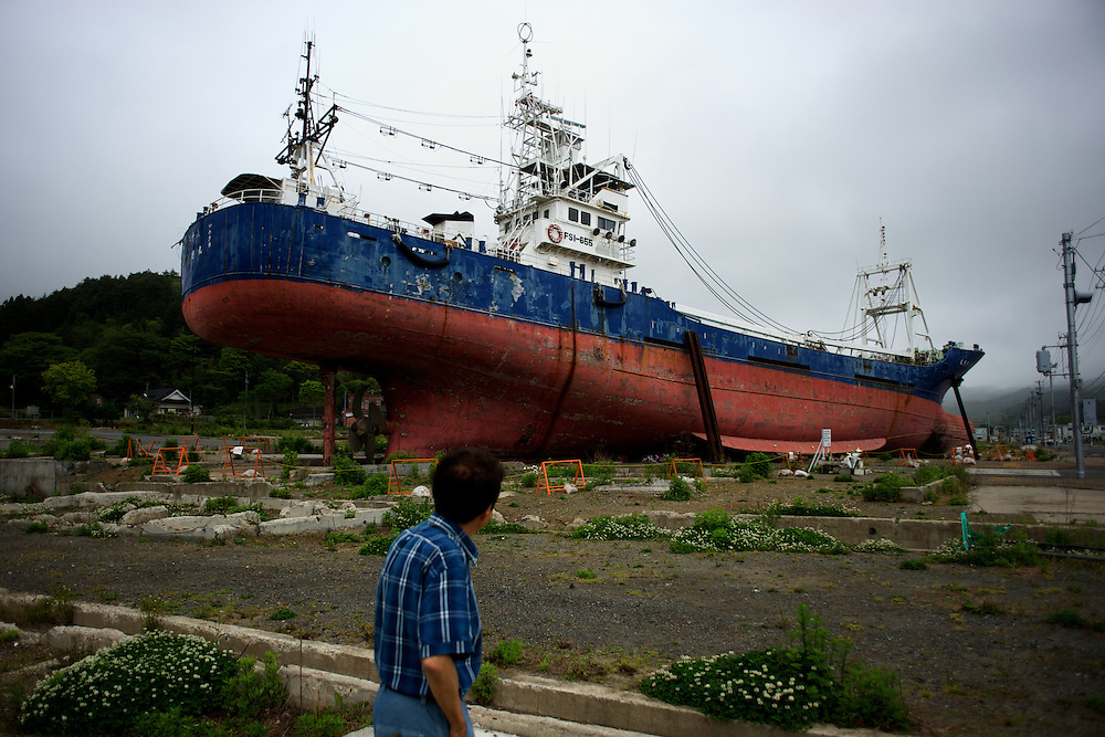 May 29, 2013 - Kesenuma, Japan: A bystander looks at a large vessel, washed away by the 2011 tsunami, grounded in what used to be a residential neighbourhood in central Kesennuma, northeastern Japan. (Paulo Nunes dos Santos)