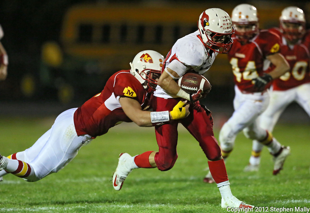 Marion's Ethan Herren (2) tries to pull down Maquoketa's Joshua Kirk (20) during the first half of the game between Maquoketa and Marion at Thomas Park Field in Marion on Friday, September 21, 2012.