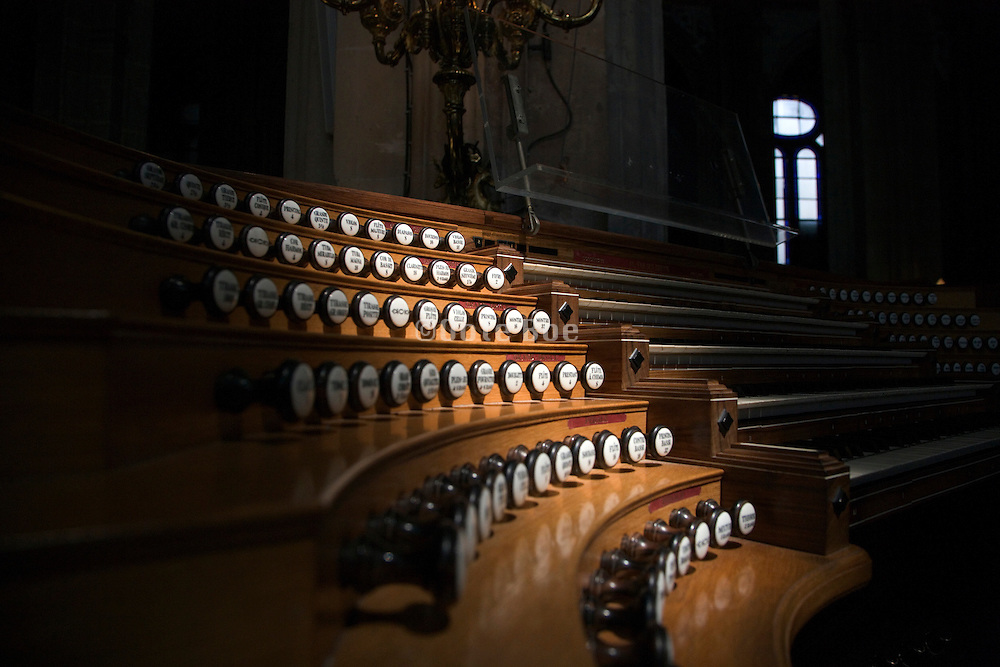 wooden organ keyboard with the pulls and stops in a church