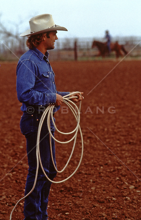 rugged cowboy with a lasso on a ranch
