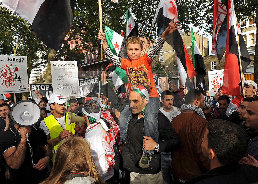 """35559258© Licensed to London News Pictures. 29/10/2011. London, UK.  A young boy sits on his father shoulders. Amnesty International join Syrians in the UK for a """"N0 More Blood - No More Fear"""" march and rally in Paddington Green, London, today 29th October 2011. Activists claim  Syrian security forces opened fire on Friday on protesters and hunted them down in house-to-house raids, killing about 40 people in the deadliest day in weeks in the country's 7-month-old uprising. Photo: Stephen Simpson/LNP"""