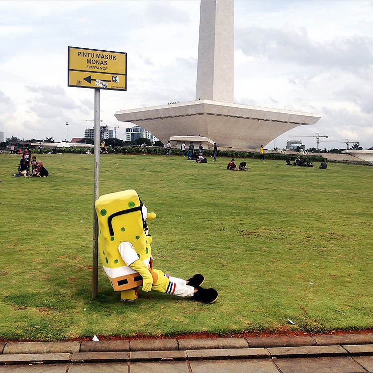 A street performer wearing a Spongebob costume rests against the Monas Entrance Sign. On average street performers earn $5-10 in tips per day posing for pictures with Monas visitors.
