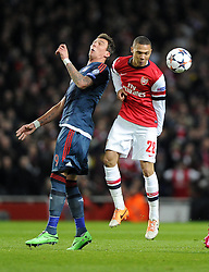Arsenal's Kieran Gibbs battles for the high ball with Bayern Munich's Mario Mandzukic - Photo mandatory by-line: Joe Meredith/JMP - Tel: Mobile: 07966 386802 19/02/2014 - SPORT - FOOTBALL - London - Emirates Stadium - Arsenal v Bayern Munich - Champions League - Last 16 - First Leg