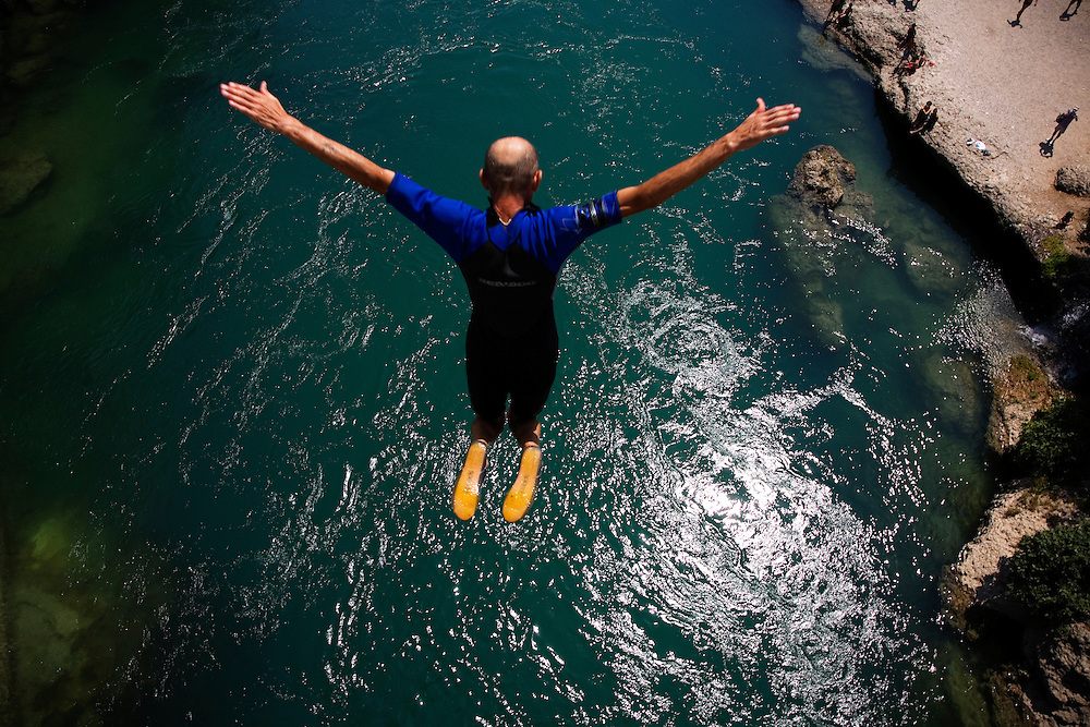 "Adem Mocca Pajevic jumps from the top of the Old Bridge on a 39* C (102* F) day into water that is around 10* C (50* F), a shock to the system that compounds the 20meter (66 feet) fall...Divers and tourists at Mostar's famous Old Bridge (Stari Most) in Bosnia and Herzegovina. This bridge is the city and region's biggest tourist attraction and there are busses full of tourists coming in from Sarajevo and Dubrovnik, Croatia. For 25euros tourists can train to jump from the bridge themselves, under supervision from the ""professional"" Mostar divers known as the Mostari. .."