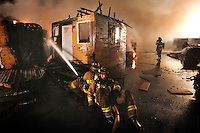 JEROME A. POLLOS/Press..Coeur d'Alene firefighter Dylan Clark supports another firefighter as they saturate a section of a fire Thursday, July 6, 2006 that completely destroyed Precision Wood Products in Coeur d'Alene, Idaho. Witness reported seeing lightening hit the main building shortly before flames began to appear.
