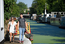© Licensed to London News Pictures. 24/07/2018. London, UK. Commuters make their way along the canal towpath at Little Venice in central London, as warm temperatures in the capital continue. Forecasters are predicting record temperatures later this week. Photo credit: Ben Cawthra/LNP