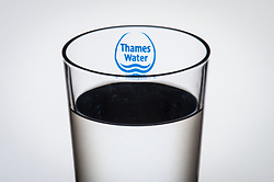 """File photo dated 02/08/16 of the logo of water company Thames Water seen through a glass of water as profits in Britain's biggest water company have crashed 86\% after a year of """"challenges"""" which saw it miss leak targets for the first time in 11 years and face a record fine for sewage pollution."""