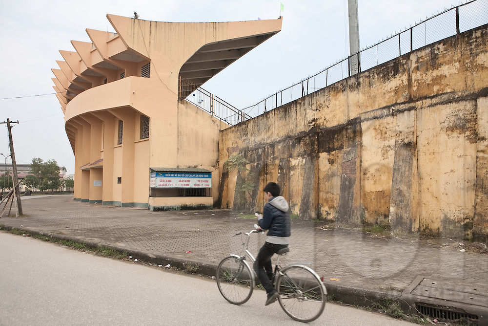 Stadium in downtown Vinh (thành c? Vinh), located in the ancient star-shaped citadel. A kid rides a bicycle. Vietnam, Asia
