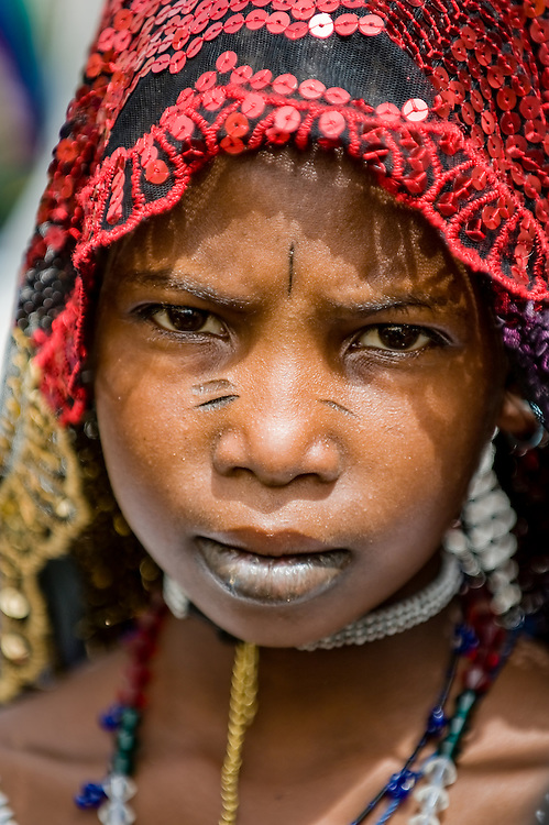 Portrait of a Fulani girl dressed in colourful traditional clothes in a local market in northern Burkina Faso. The Fulani or Peul are nomadic herdsmen of the Sahel region of West Africa. The darker lower lip from indigo staining, facial tattoos and silver jewellery are traditional markings of Fulani women.