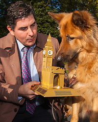 London, October 23rd 2014. Organised by the Dogs Trust and the Kennel Club, politicians  and their pooches gather outside Parliament for the 22nd Westminster Dog of the Year competition, aimed at raising awareness of dog welfare in the UK where the Dogs Trust cares for over 16,000 stray and abandoned dogs annually. PICTURED: Winners Diesel and Rob Flello MP (Stoke-on-Trent South) examine their Westminster Dog of the Year trophy.